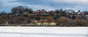 Дома на утесе с другой стороны замороженного реки Стоковые Фото