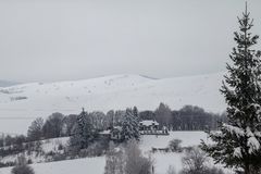 Дома на холме покрытом со снегом и окруженном лесом стоковое изображение rf