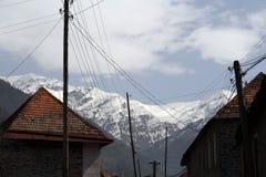 Дома приближают к горе под пасмурным голубым небом Стоковая Фотография