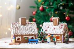 2 дома пряника, дерево и люд сидя на стенде, wint Стоковая Фотография