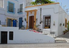 Дома с белыми стенами покрасили двери и цветочные горшки в Nijar в Андалусии (Испания) Стоковое Изображение