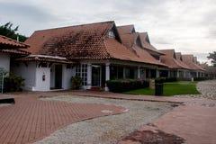 Дома с красивыми плитками глины, с красными вымощая камнями и зелеными лужайками Стоковые Фото