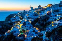 Дома Cycladic вдоль скалы Oia, Santorini, Греции Стоковая Фотография
