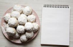 Домодельные белые мексиканские печенья свадьбы и пустой блокнот над белой деревянной предпосылкой, надземным взглядом Плоское пол стоковые фотографии rf