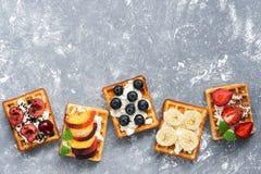 Домодельные бельгийские waffles с разнообразие плодоовощами на серой предпосылке Взгляд сверху, космос экземпляра Стоковое Фото