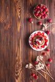 Домодельные блинчики с клубниками, взбитой сливк и отбензиниванием шоколада, украшенными с цветками на деревянной предпосылке Стоковое Изображение