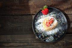 Домодельные блинчики с клубниками, голубиками и напудренным сахаром помадка завтрака стоковые фото