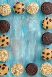 Домодельные булочки обломока шоколада как рамка на голубом деревянном столе Стоковые Изображения