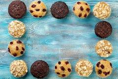 Домодельные булочки обломока шоколада как рамка на голубом деревянном столе Стоковые Изображения RF