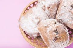 Домодельные булочки с изюминками и напудренным сахаром в плетеной корзине на свете - розовой предпосылкой Стоковое Фото