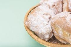 Домодельные булочки с изюминками и порошок сахара в плетеной корзине против светлого цвета мяты Стоковое Изображение RF