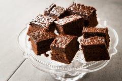 Домодельные влажные части пирожного торта губки шоколада в винтажной стеклянной стойке десерта Стоковые Фотографии RF