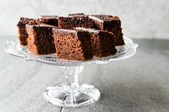 Домодельные влажные части пирожного торта губки шоколада в винтажной стеклянной стойке десерта Стоковые Фото
