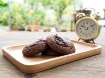 Домодельные мягкие темные печенья пирожного шоколада помещенные на деревянной плите на деревянном столе За печеньями имейте cloc  Стоковое Изображение