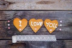Домодельные печенья в форме сердца с letteing я тебя люблю и сердец конфеты сахара помадок, винтажной ленты на деревенское деревя Стоковое фото RF