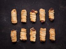 домодельные печенья: несколько сосисок в тесте на черной предпосылке Стоковые Изображения
