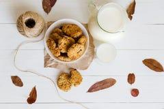 Домодельные печенья овсяной каши с изюминками и черносливами с кувшином и стеклом молока на белой деревянной предпосылке Отсутств Стоковые Изображения