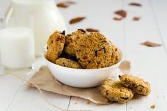 Домодельные печенья овсяной каши с изюминками и черносливами с кувшином и стеклом молока на белой деревянной предпосылке Отсутств Стоковые Фотографии RF