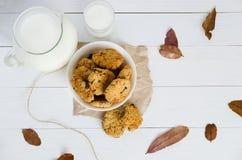 Домодельные печенья овсяной каши с изюминками и черносливами с кувшином и стеклом молока на белой деревянной предпосылке Отсутств Стоковые Изображения RF