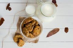 Домодельные печенья овсяной каши с изюминками и черносливами с кувшином и стеклом молока на белой деревянной предпосылке Отсутств Стоковая Фотография