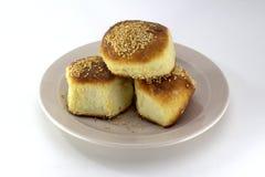 Домодельные печенья, румяные плюшки с семенами сезама на плите жемчуга на белой предпосылке Стоковые Фото