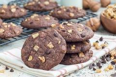 Домодельные печенья шоколада с грецкими орехами и обломоками шоколада на таблице и охладительной решетке, горизонтальных Стоковое фото RF