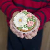 Домодельные пирожные губки с замораживать buttercream цветков Мальчик держит украшенное пирожное Сладкий подарок к маме стоковые изображения rf