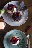 Домодельные пирожные с свежими ягодами в плитах на деревянном столе Стоковая Фотография