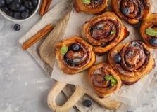 Домодельные плюшки циннамона с голубиками и циннамоном на белизне Стоковые Изображения RF