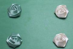 Домодельные розы от белой и изумрудной сатинировки Расположитесь на углах рамки На зеленой предпосылке Стоковая Фотография RF