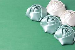 Домодельные розы от белой и изумрудной сатинировки Расположитесь на правом угле рамки На зеленой предпосылке Стоковые Фото