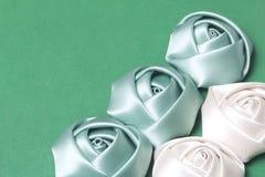 Домодельные розы от белой и изумрудной сатинировки Расположитесь на правом угле рамки На зеленой предпосылке Стоковая Фотография RF