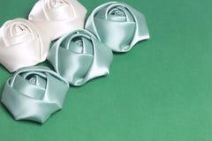 Домодельные розы от белой и изумрудной сатинировки Расположитесь на левом угле рамки На зеленой предпосылке Стоковые Фото