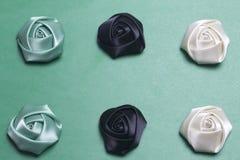 Домодельные розы от белой, черной и изумрудной сатинировки На зеленой предпосылке Стоковое Фото