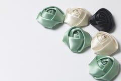 Домодельные розы от белой, черной и изумрудной сатинировки Расположитесь на правом угле рамки На белой предпосылке Стоковая Фотография
