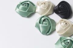 Домодельные розы от белой, черной и изумрудной сатинировки Расположитесь на правом угле рамки На белой предпосылке Стоковая Фотография RF