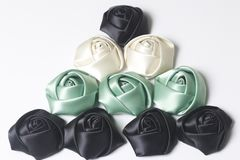 Домодельные розы от белой, черной и изумрудной сатинировки Расположитесь в форме пирамиды На белой предпосылке Стоковое Изображение RF