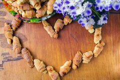 Домодельные свежие печенья в форме цветков сердца и фиолетов на деревянной доске с космосом экземпляра, взгляд сверху Стоковое Фото