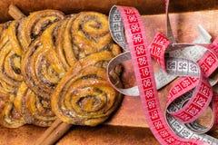 домодельные сладостные крены циннамона на красной плите с ручками cinnamons и рулетки пустыни Стоковая Фотография RF