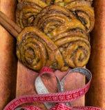 домодельные сладостные крены циннамона на красной плите с ручками cinnamons и рулетки пустыни Стоковая Фотография