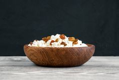 Домодельные творог или творог с изюминками в шаре на белом деревянном столе с черной предпосылкой органическое еды здоровое Стоковое фото RF