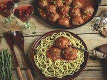 Домодельные фрикадельки в томатном соусе с макаронными изделиями на плите деревянное сковороды поверхностное стоковое фото rf