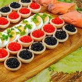 Домодельные tartlets с красной и черной икрой, семгой, салатом и Стоковая Фотография