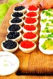 Домодельные tartlets с красной и черной икрой, семгой, салатом и Стоковые Фотографии RF