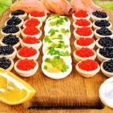 Домодельные tartlets с красной и черной икрой, семгой, салатом и Стоковое Фото