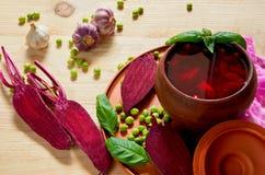 Домодельный борщ с овощами на деревянной предпосылке украшенной с свежей отрезанной свеклой, чесноком, листьями базилика и зелены стоковые фото