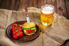 Домодельный бургер говядины и свежие овощи на блюде глины с glas Стоковая Фотография RF