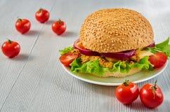 Домодельный вегетарианский бургер с салатом, кольцами лука, сыром, томатами вишни и мустардом на серой конкретной предпосылке Стоковая Фотография RF