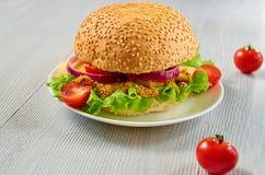 Домодельный вкусный вегетарианский бургер с салатом, кольцами лука, сыром, томатами вишни и мустардом на серой предпосылке Стоковая Фотография