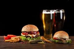 Домодельный гамбургер с французским картофелем фри и 2 стеклами пива на деревянном столе стоковое фото